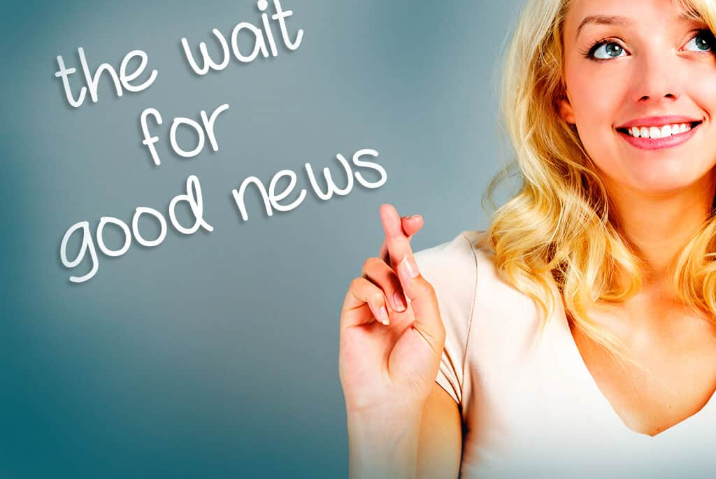 A woman crossing her fingers and the text the wait for good news