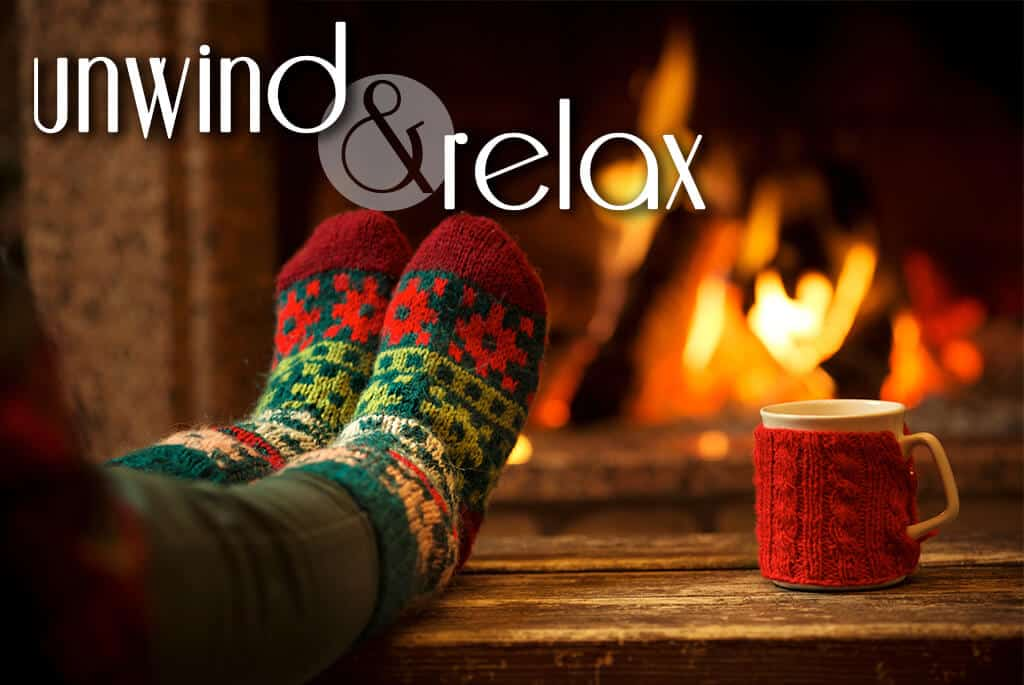 feet in red and green warm socks on a wooden bench with a mug in a knitted cozy in front of a fireplace, the text reads unwind and relax