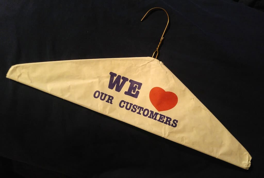 a wire hanger with a paper cover that reads we heart our customers